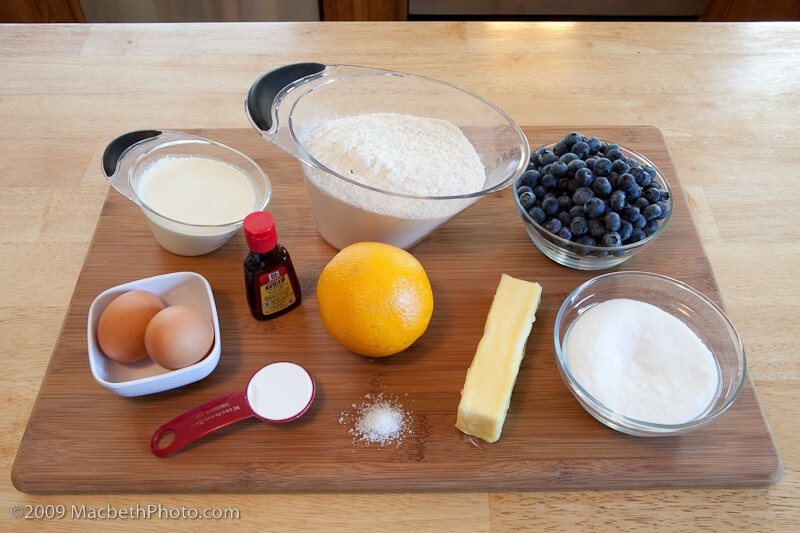 Blueberry Citrus Scones Ingredients measured out on cutting board with separate containers holding milk, flour, eggs, baking soda, vanilla, orange, butter, salt, sugar, and blueberries.