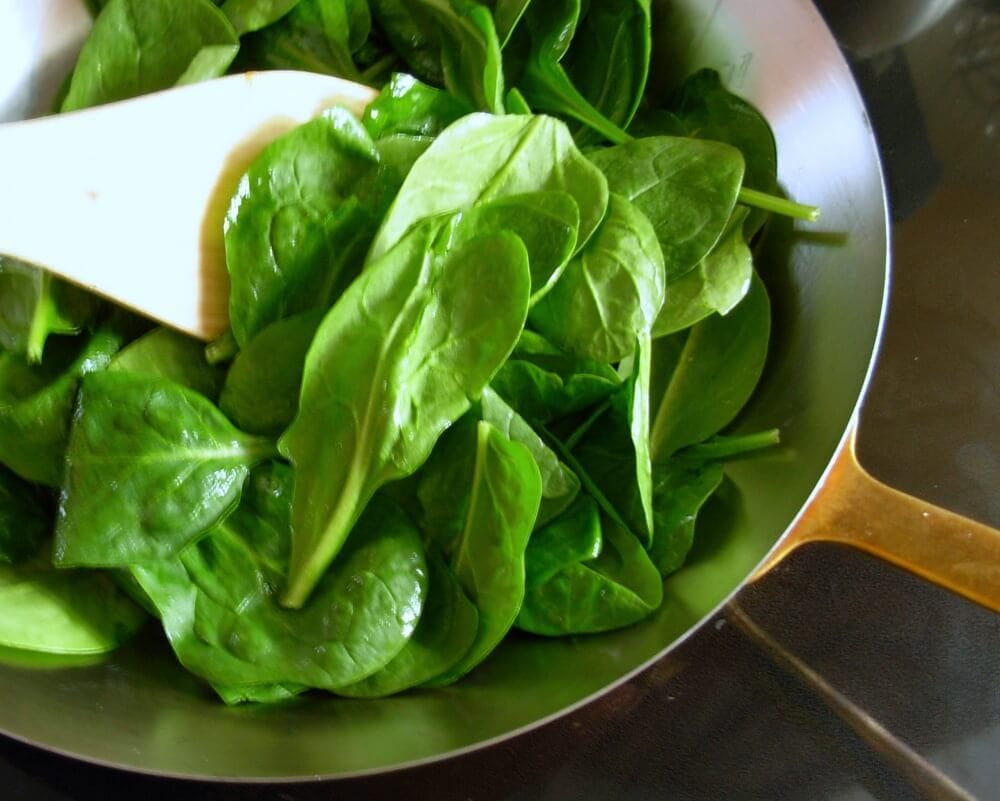 Cooking spinach in sauté pan.