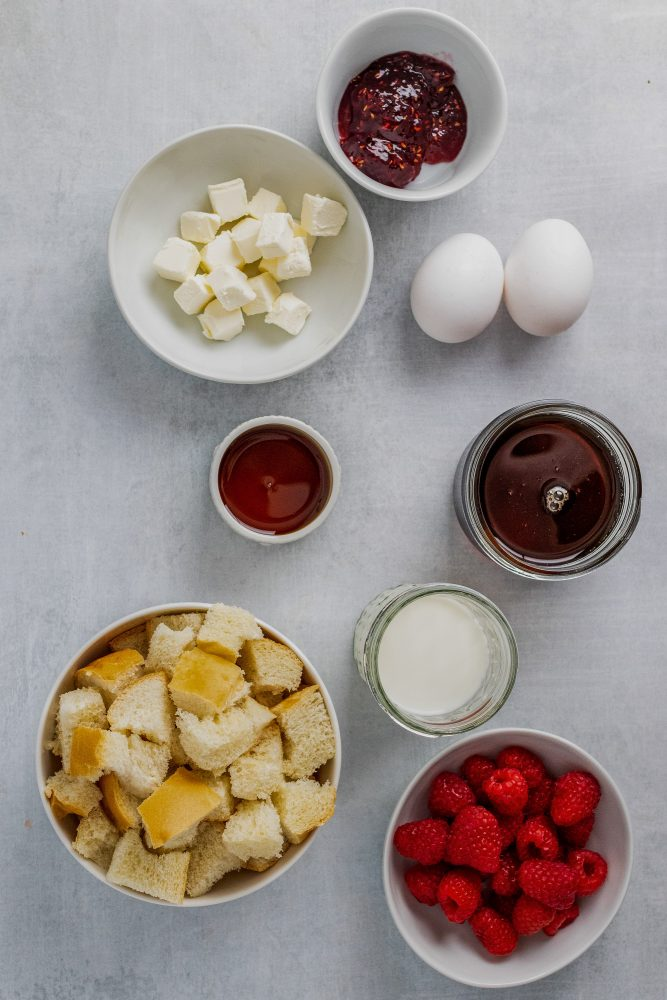 Overhead view of pre-measured ingredients including raspberry preserves, cubed cream cheese, two eggs, maple syrup, cubed French bread, milk, and fresh raspberries.
