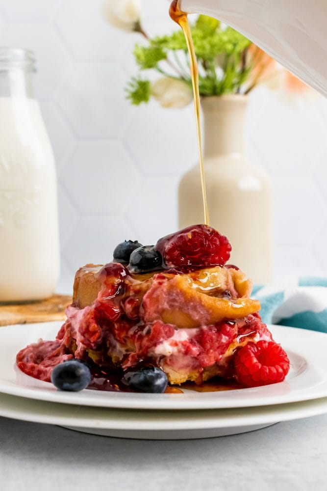 Side view of pouring maple syrup onto cream cheese stuffed french toast topped with raspberries and blueberries.