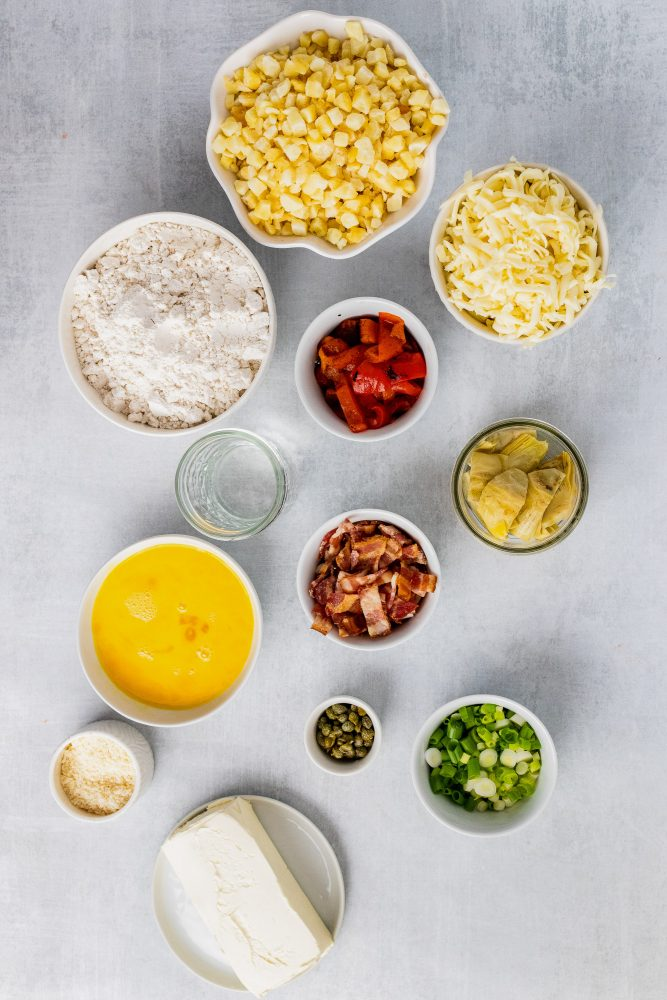 Overhead shot of ingredients including frozen hash browns, biscuit mix, roasted red peppers, mozzarella cheese, quartered artichokes, chopped bacon, scrambled eggs, chopped green onions, Parmesan cheese, and cream cheese.