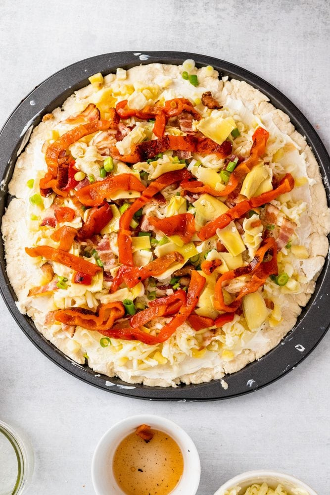 Overhead shot of other ingredients added on top of pizza including roasted red peppers, artichokes, and green onions.