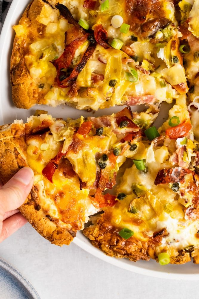 Close up of hand taking a slice of breakfast pizza.