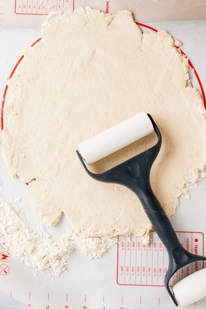 Overhead look at rolling out the biscuit dough flat to place into a round pan.