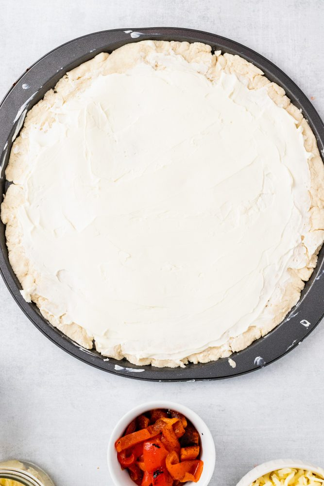 Overhead shot of spreading the softened cream cheese onto the dough.