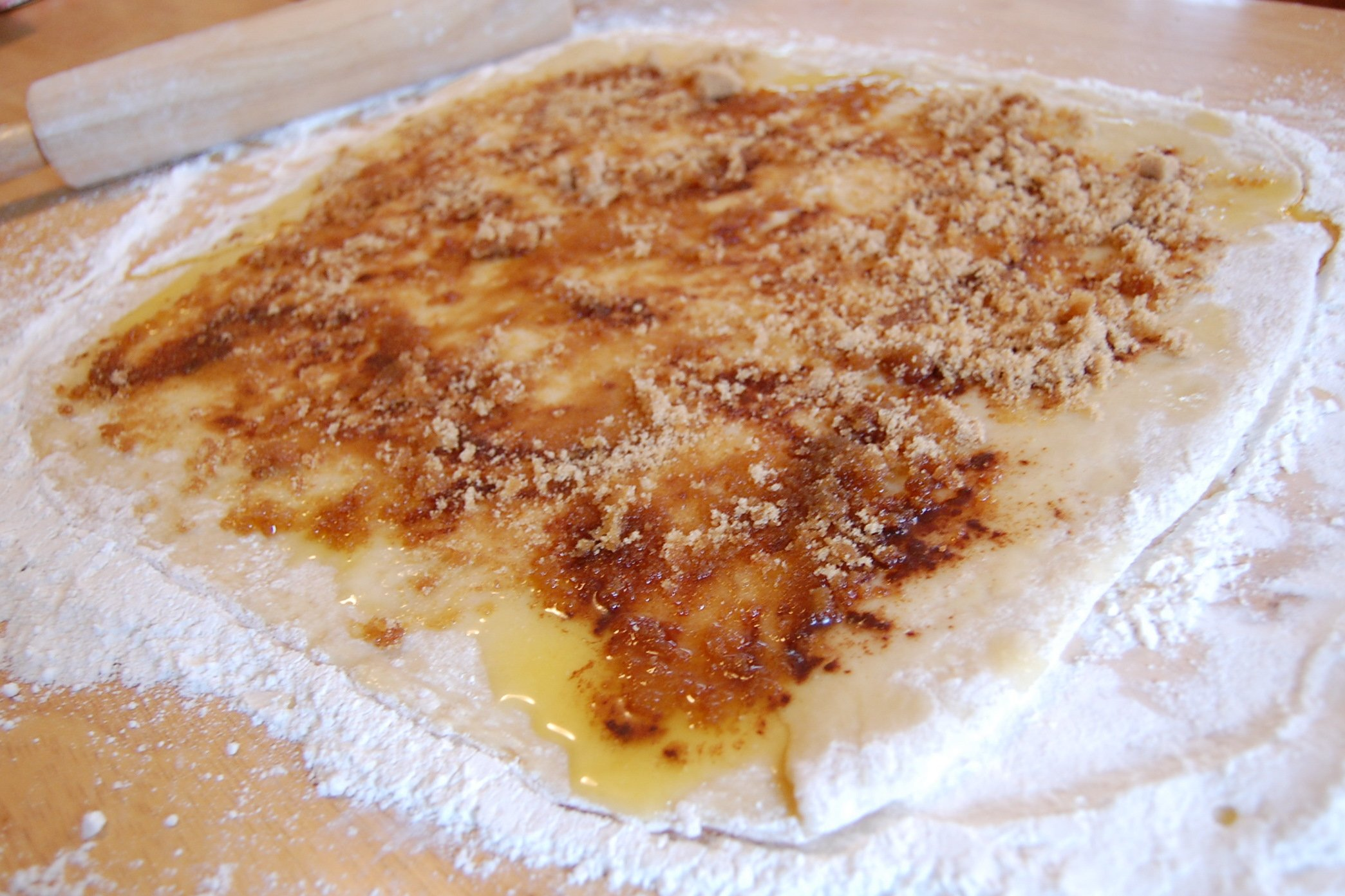 Dough with melted butter and cinnamon spread on top.