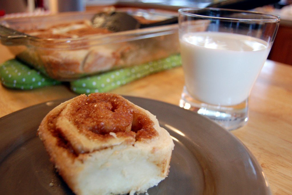 Baked homemade cinnamon roll with a glass of milk.