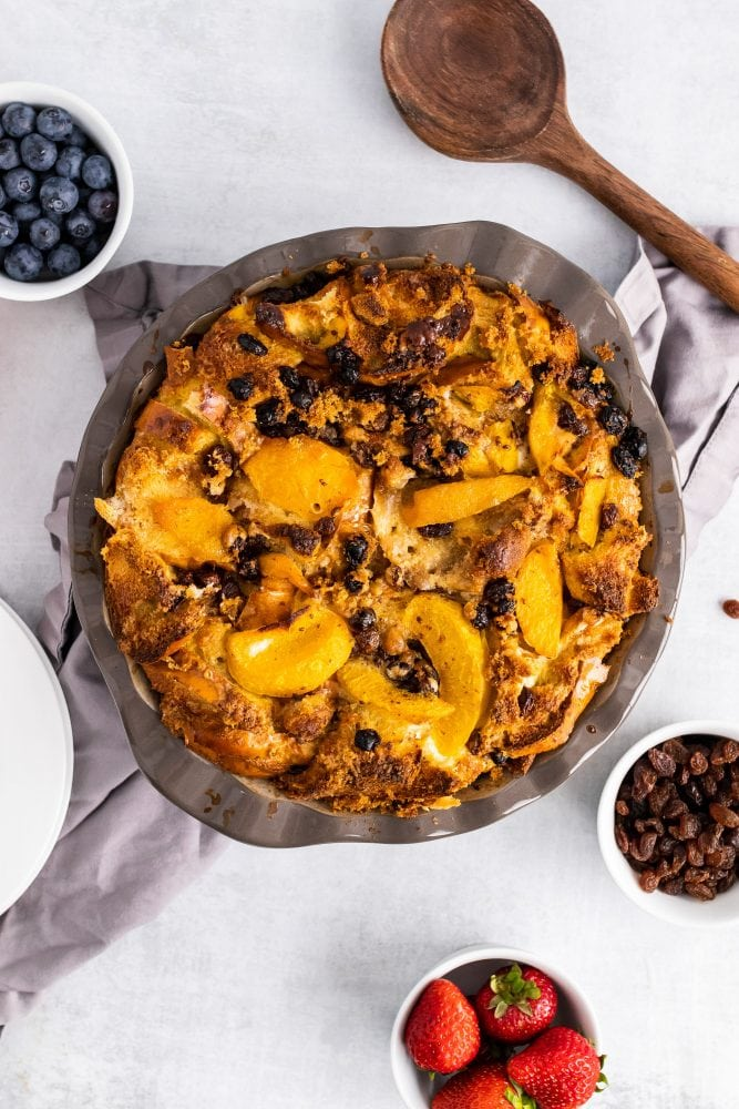 Overhead shot of bourbon bread pudding with peaches fresh baked out of the oven.