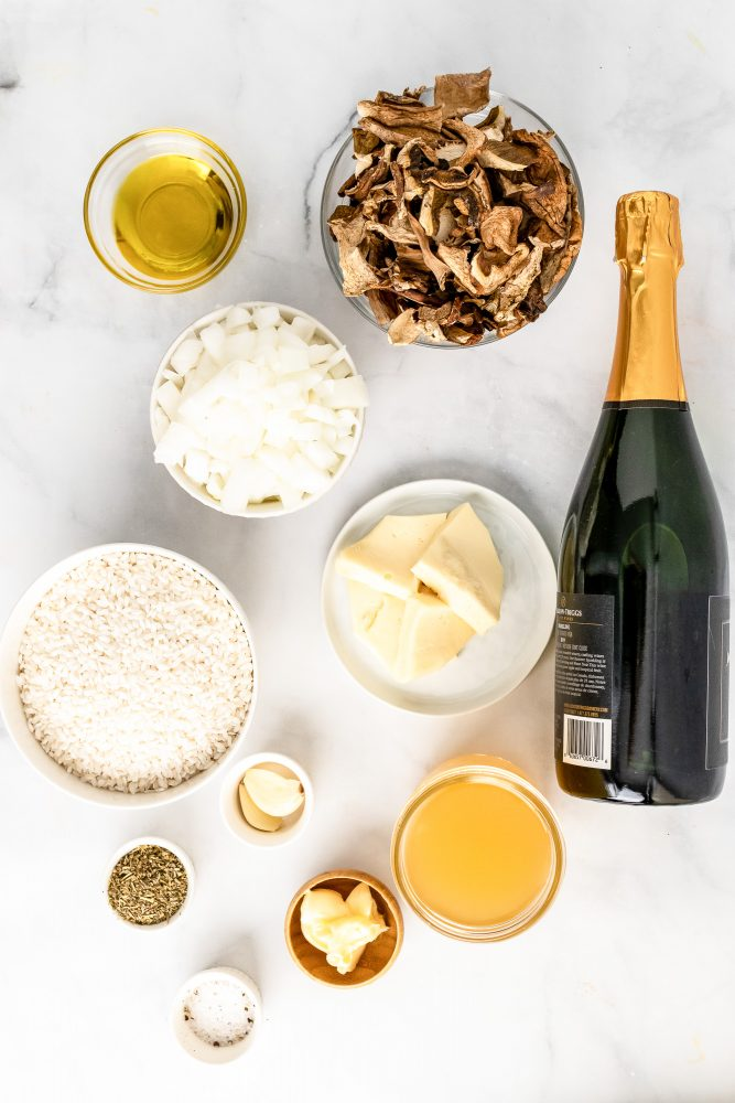 Overhead look at ingredients needed for Champagne risotto including olive oil, Champagne, dried mushrooms, diced onions, butter, short grain rice, garlic, salt, Italian seasoning, and broth.