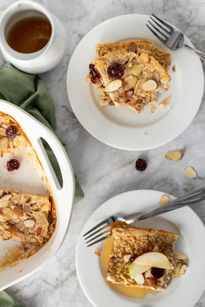 Overhead shots of two servings of baked oatmeal on plates with a side of maple syrup.