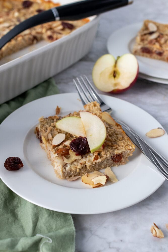 A slice of baked oatmeal on a white plate, topped with apple slices.