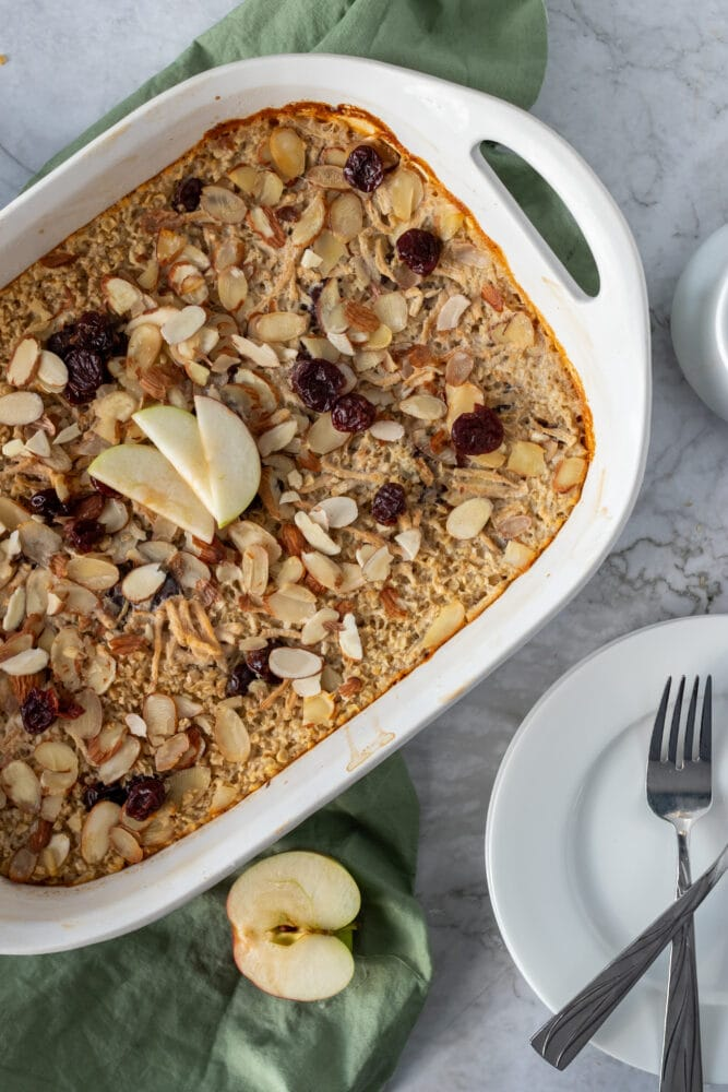 Overhead shot of cherry almond oatmeal bake with sage green towel, sliced apple, dried cherries, and toasted almonds.