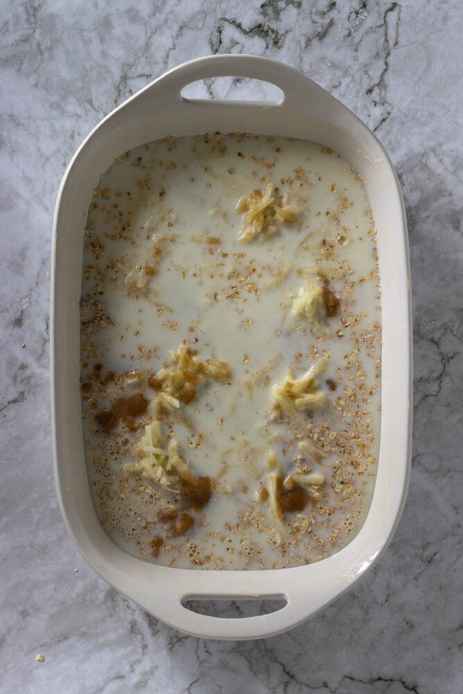 Overhead shot of milk, oatmeal, grated apple, and brown sugar in baking dish.