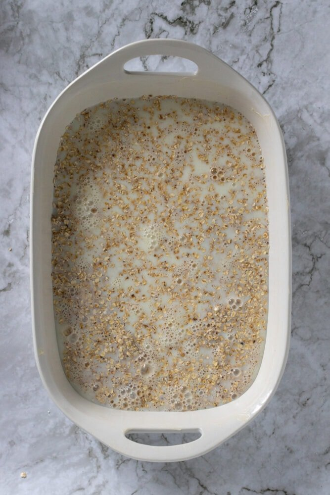 Overhead shot of milk mixed with oatmeal in casserole dish.