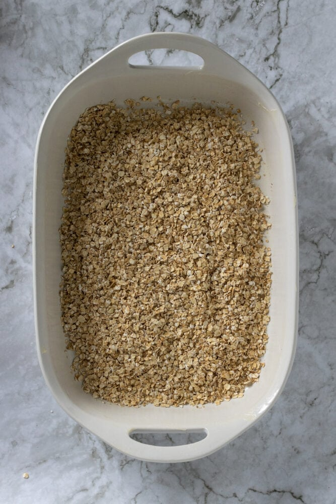 Overhead shot of dry oatmeal in casserole dish.