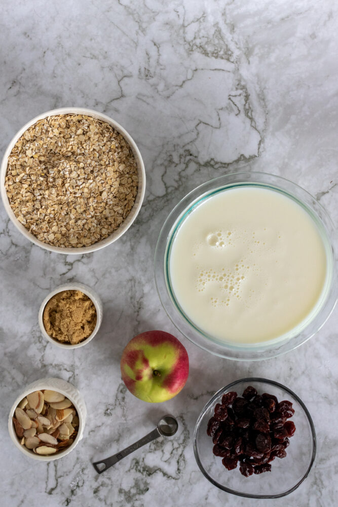 Overhead shot of ingredients for oatmeal bake including: oatmeal, milk, brown sugar, apple, dried cherries, and sliced almonds.