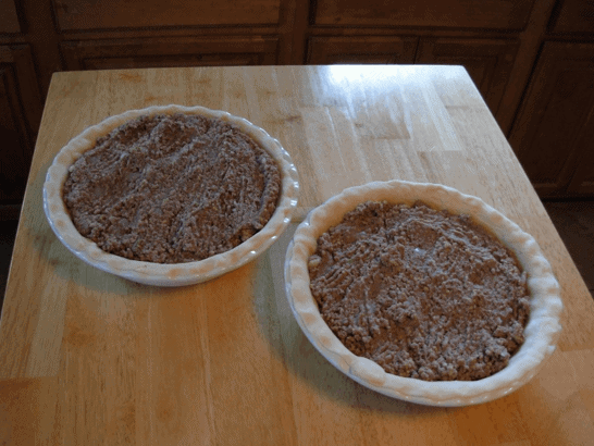 Two uncooked pie crusts with the meat and potato filling spooned in and ready to be baked.