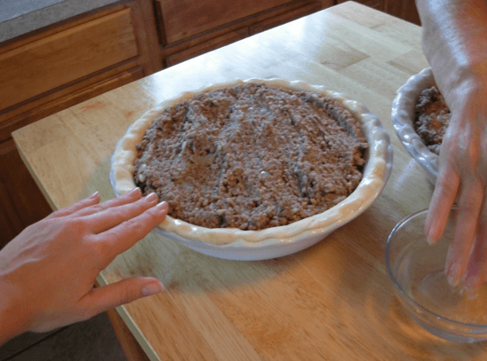 Preparing the bottom pie crust for the top by dipping our fingers in water and gently patting and getting the edge of the bottom pie crust wet.