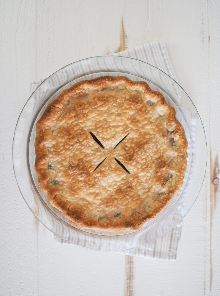 Overhead photo of a whole tourtiere (meat pie) unsliced and cooling on a white and grey striped towel.