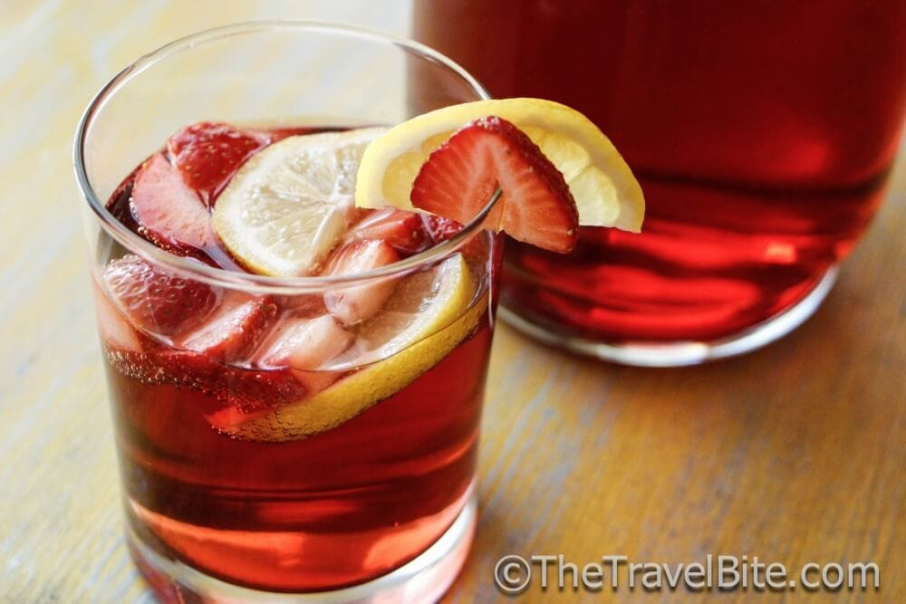 Glass of red sparkling summer sangria with lemon and strawberry slices as garnish.
