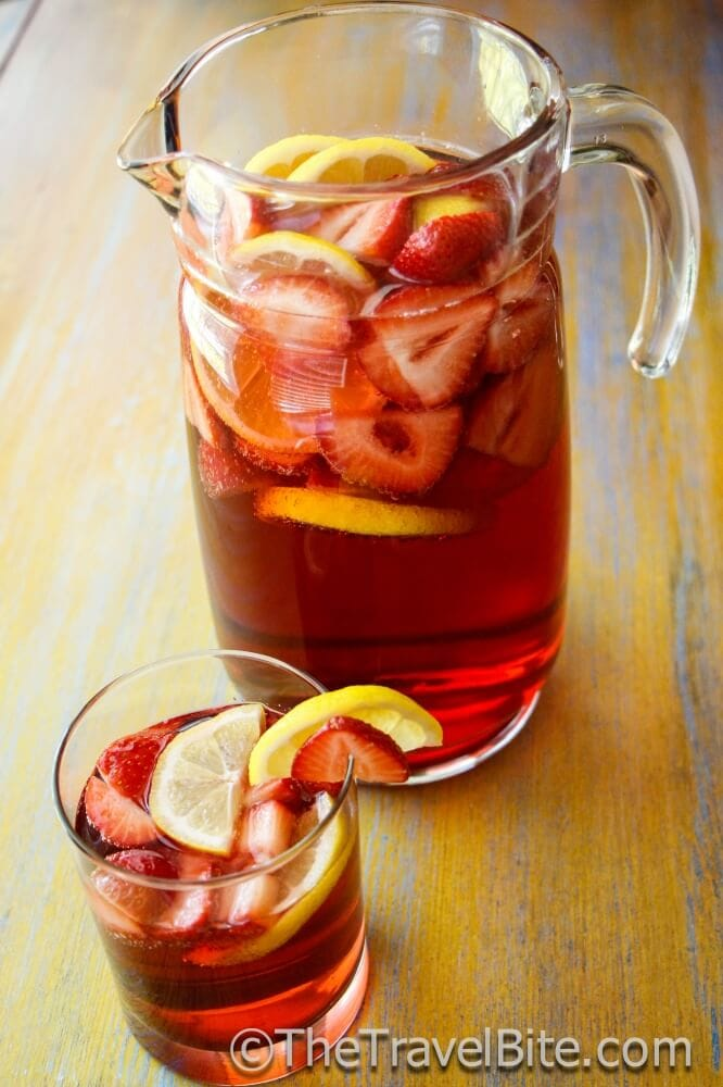 Pitcher of Sparkling Summer Sangria with slices of lemon and strawberry.