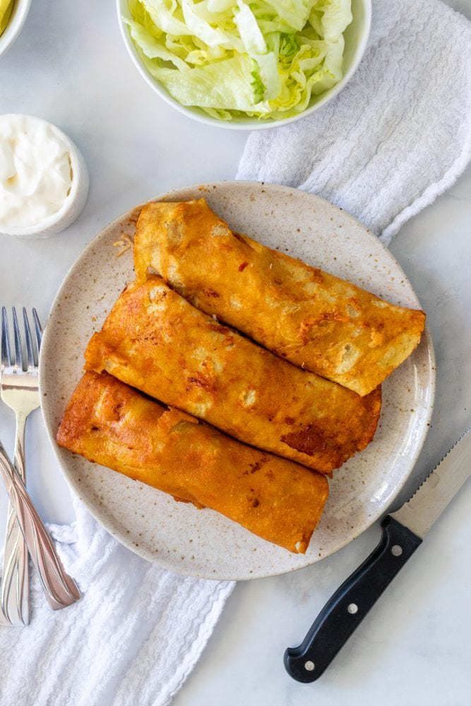 Three enchiladas rolled onto a plate, ready for toppings.