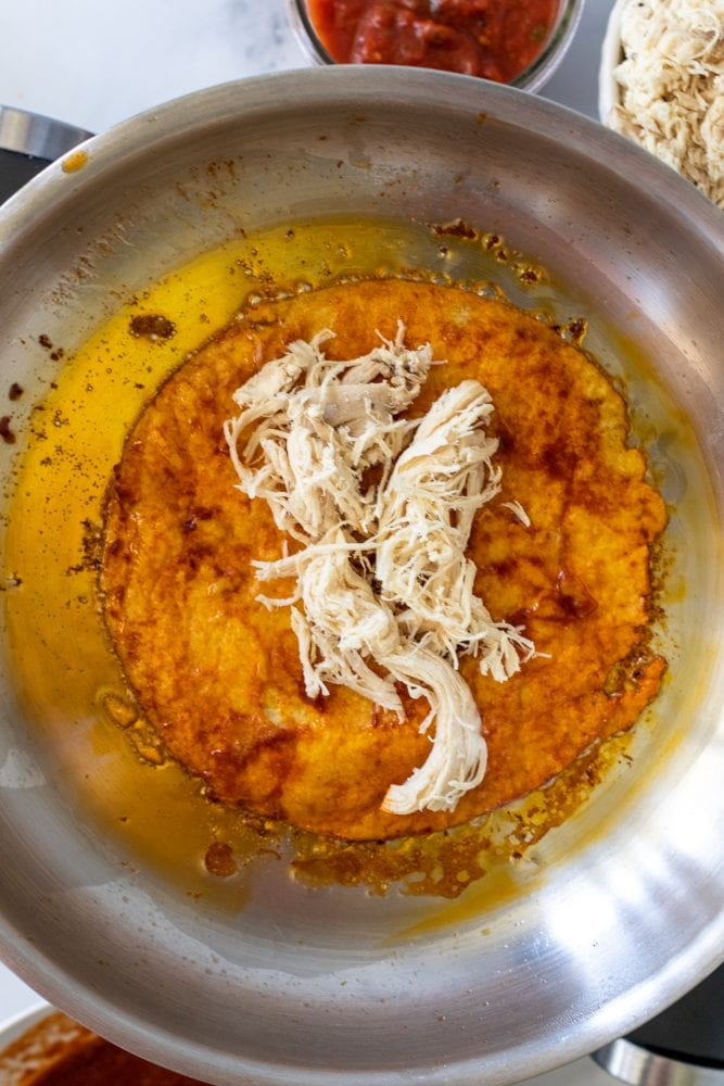 Adding pre-cooked shredded chicken to the cooked tortilla in a sauce pan.
