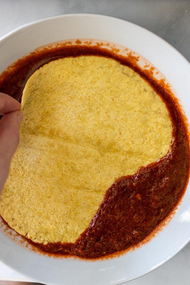 Overhead shot of dipping corn tortilla into enchilada sauce.