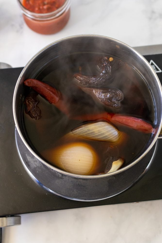 Chilis, white onion, and garlic in a saucepan filled with water softened from boiling.