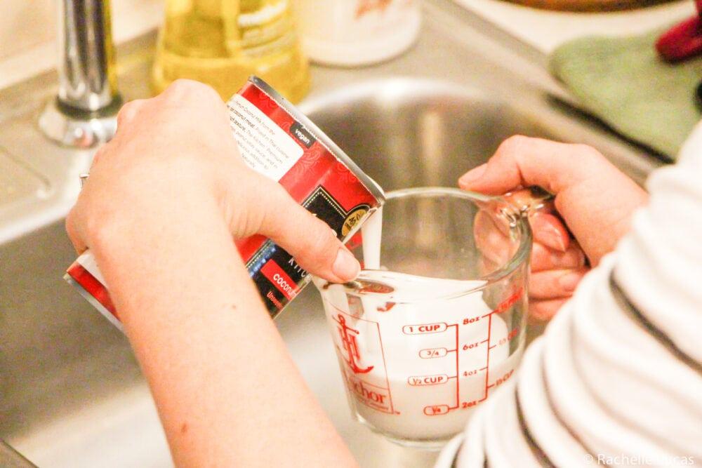 Measuring coconut milk for recipe.