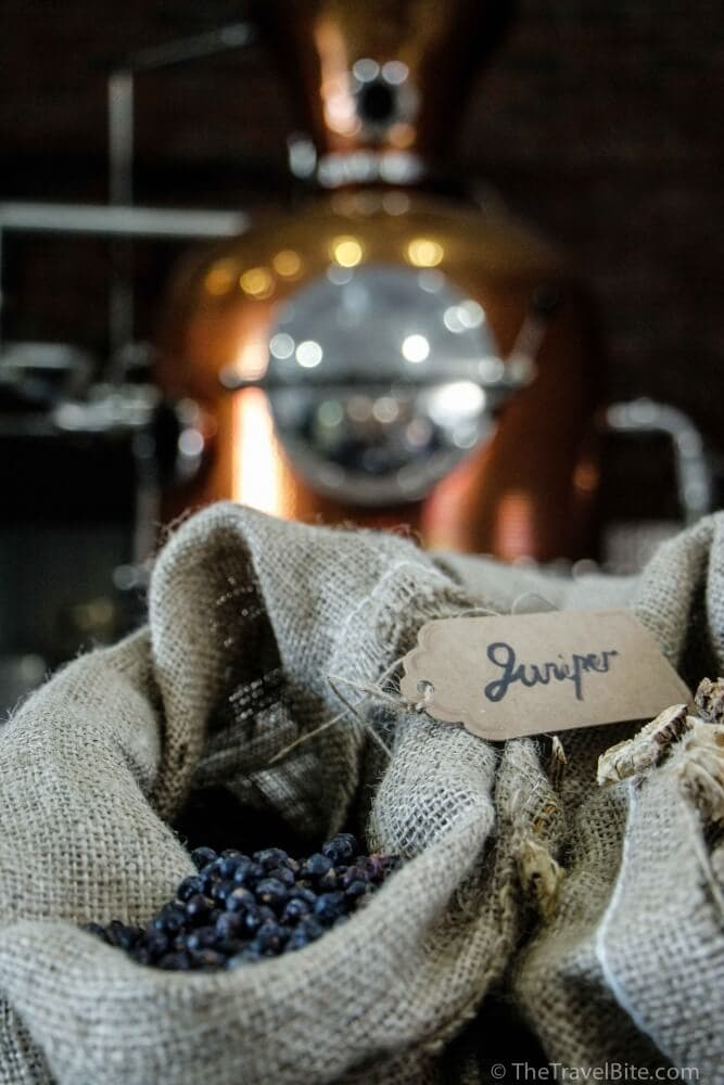 A sack of juniper berries sitting next to a copper pot still.