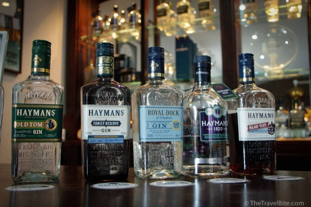 Different types of gin lined up on a bar included Old Tom gin, Hayman's Family Reserve, Royal Dock Gin, Haymans 1820, and Hayman's Sloe Gin.