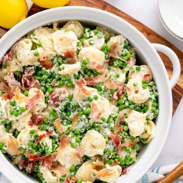 Overhead shot of one large serving bowl filled with lemon pasta with pancetta and peas.