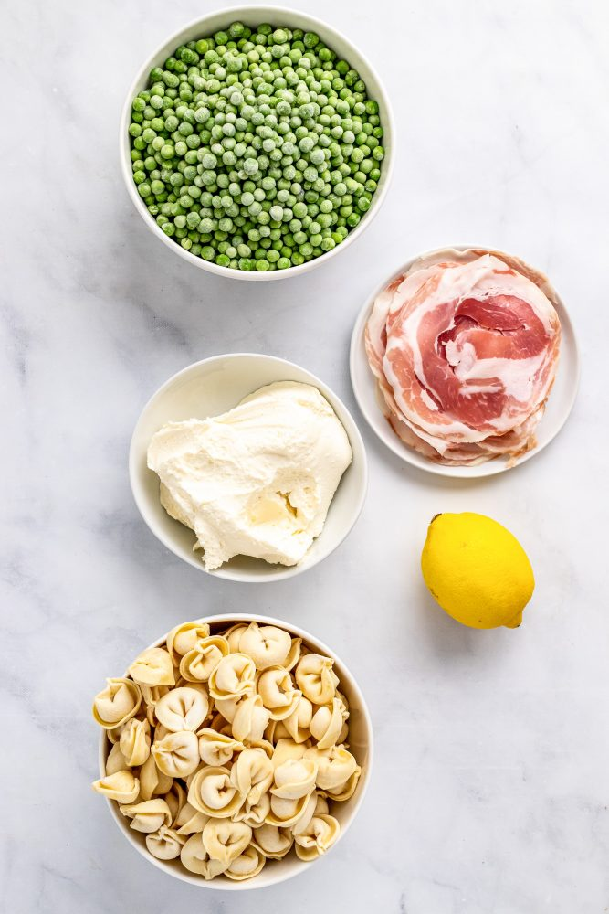 Overhead look at all 5 ingredients for this recipe: peas, pancetta, mascarpone cheese, one whole lemon, tortellini.