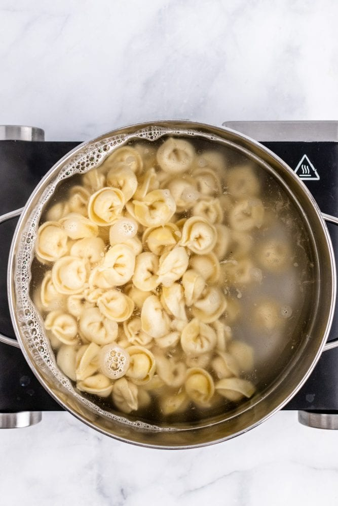 Overhead look at a pot of boiling water filled with tortellini.