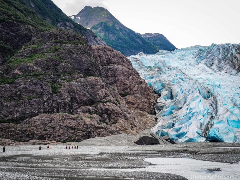 Hikers walking the rocky shoreline to Davidson Glacier.