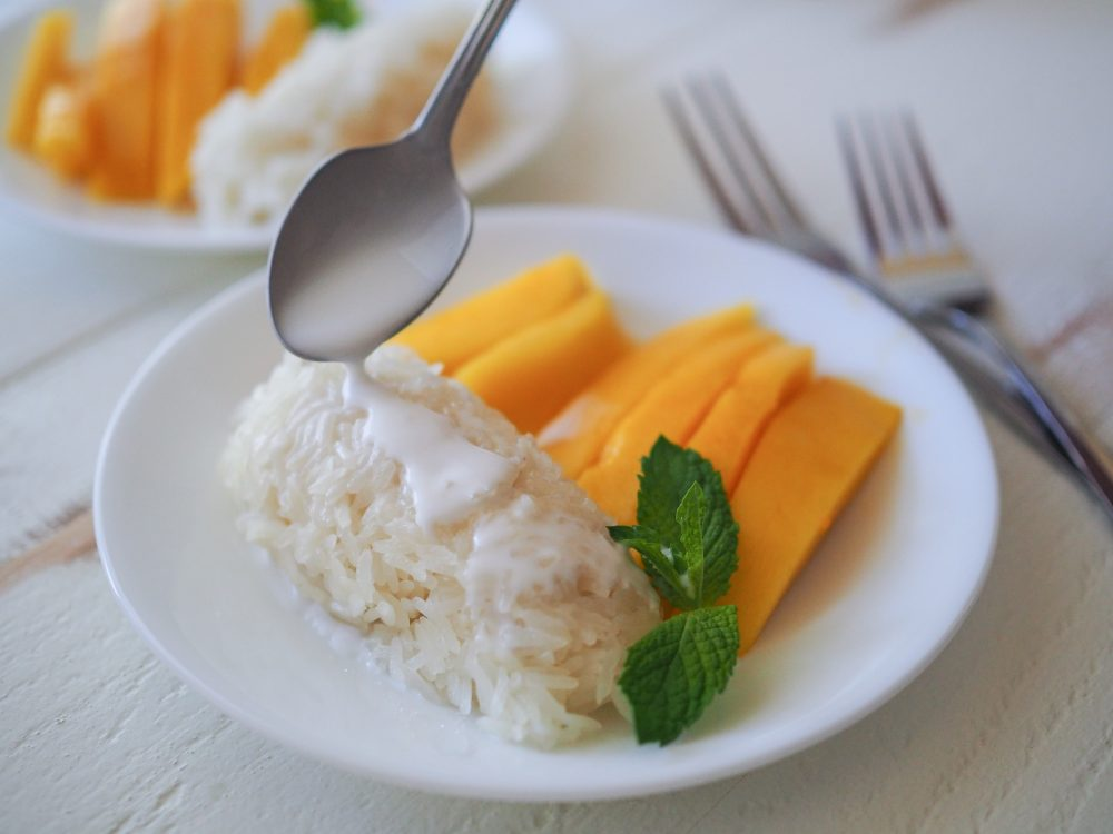 Adding more coconut milk to sticky rice with a spoon.