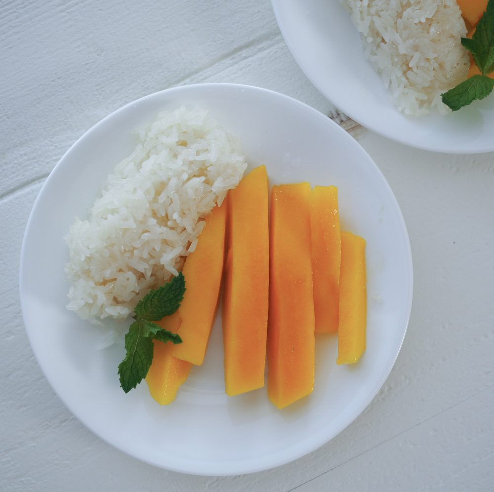 Sticky rice and mango with mint on a plate.
