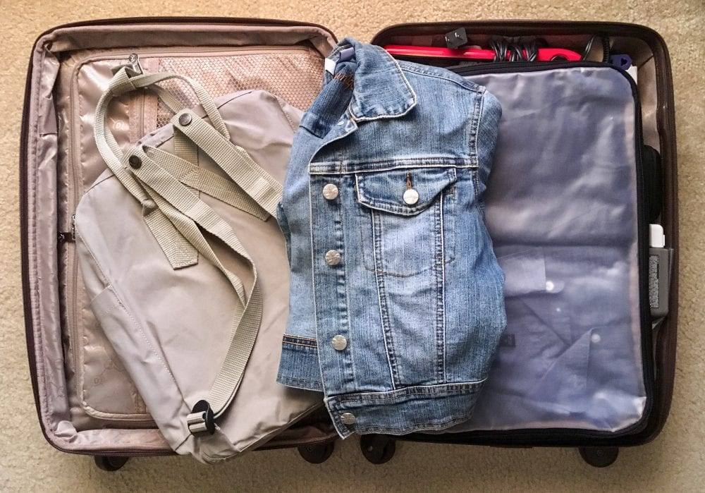 Overhead shot of an open suitcase showing an empty backpack, folded up jean jacket, packing cube filled with shirts, and a hair flat iron.