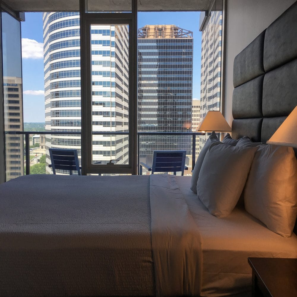 View of bedroom and balcony looking out at skyscraper office buildings in Nashville from AirBnB room.