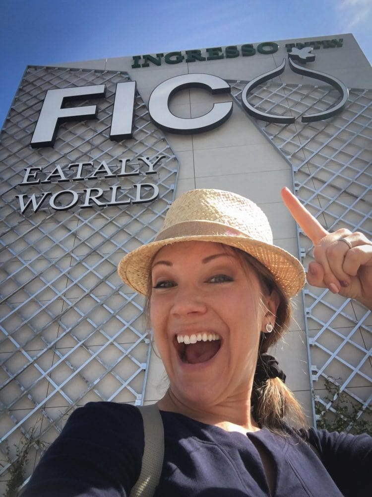 Rachelle Lucas of TheTravelBite.com standing in front of the sign for FICO Eataly World.