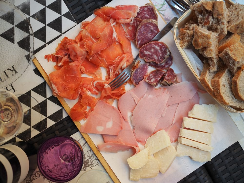 A Bolognese charcuterie board of mortadella and other cured meats along with chunks of parmiggiano reggiano cheese.