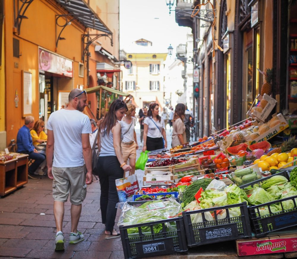 Shoppers in a Bologna outdoor food market looking at vegetables.