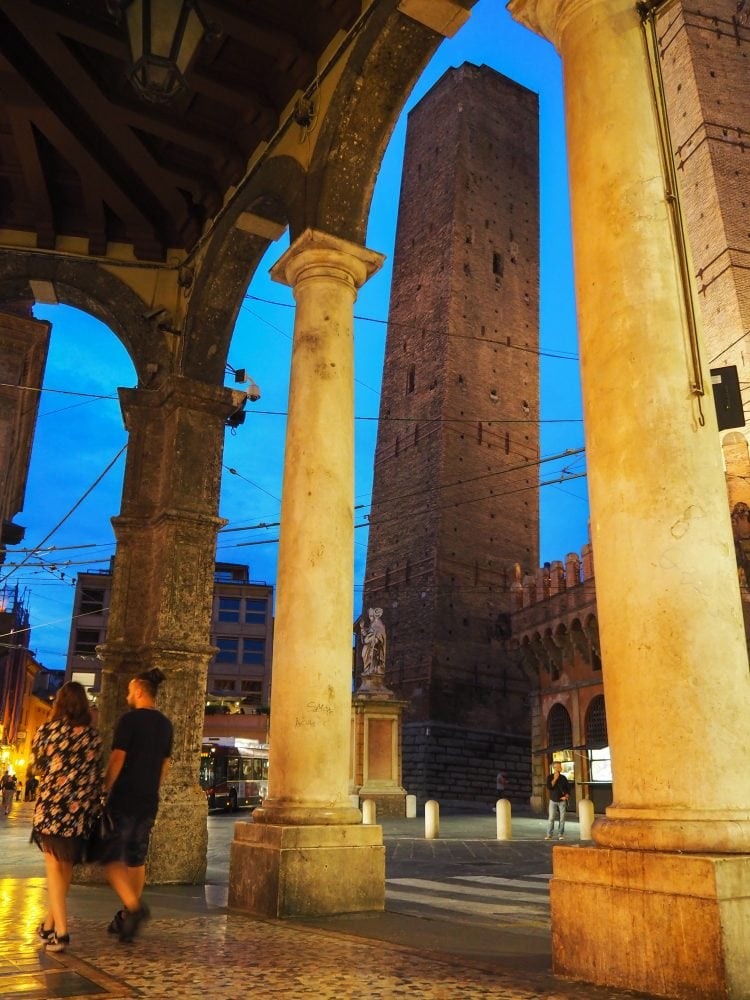 A photo of one of Bologna's two towers at twilight from underneath the porticoes.