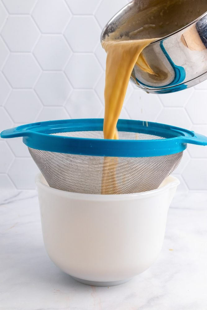 Pouring gelato base through sieve into a container.