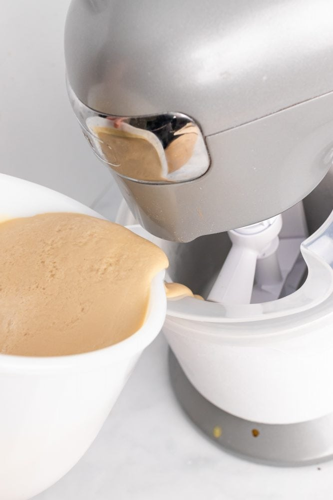 Pouring gelato base into a frozen stand mixer ice cream making bowl.