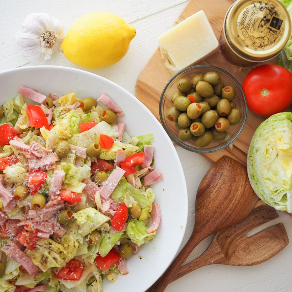 Overhead look at a big bowl of the 1905 salad with romaine lettuce, cubes of ham, Spanish olives, diced tomatoes, and grated parmesan cheese.