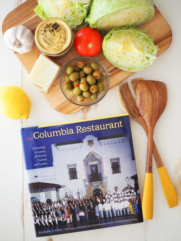 A picture of the Columbia Restaurant cookbook with a cutting board holding the ingredients.