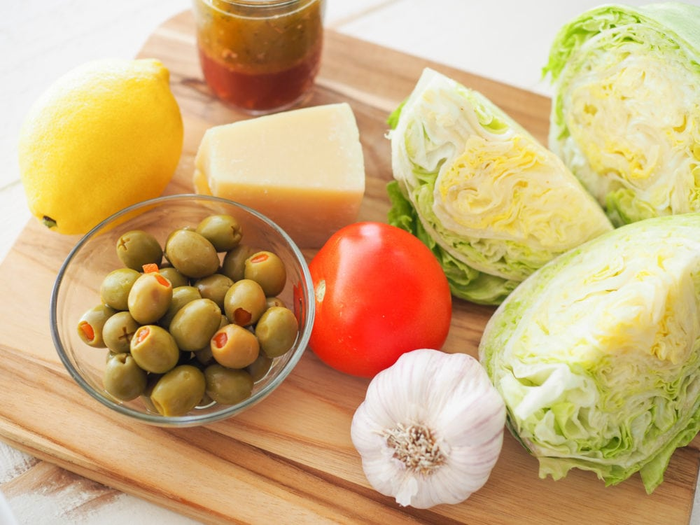 Ingredients for the 1905 Salad on a cutting board: Spanish Olives, Lemon, Parmesan Cheese, Tomato, Garlic, Lettuce.