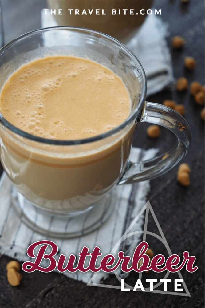 Pinterest Pin of Hot butterbeer in a clear glass mug with a French Press coffee maker and sprinkles of butterscotch chips.